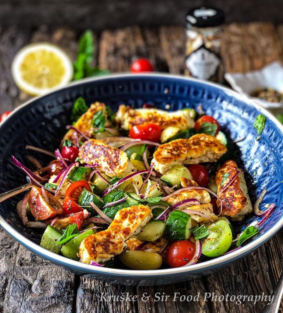 Salata sa grilovanim halumi sirom i paradajzom, servirana u grčko plavoj posudi