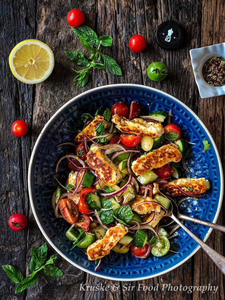 Salata sa grilovanim halumi sirom i paradajzom, servirana na tradicionalan način, uz kriške limuna i čeri paradajz
